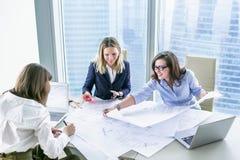 Geschäftsfrauen, die mit Geschäftszeichnungen im modernen Büro arbeiten Lizenzfreie Stockfotos