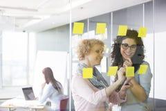 Geschäftsfrauen, die mit klebrigen Anmerkungen im Büro gedanklich lösen Lizenzfreie Stockfotografie