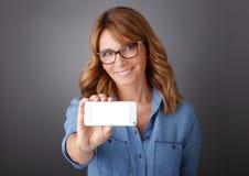 Geschäftsfrauen, die newspaer lesen und Mobile anhalten Stockbilder