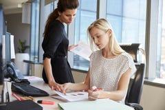 Geschäftsfrauen, die am Schreibtisch auf Computer zusammenarbeiten Stockfotos