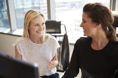 Geschäftsfrauen, die am Schreibtisch auf Computer zusammenarbeiten Lizenzfreies Stockbild