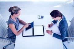 Geschäftsfrauen, die am Schreibtisch zusammenarbeiten Stockfotografie