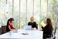 Geschäftsfrauen, die sich bei Tisch im Büro besprechen stockbilder