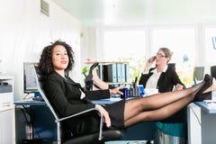 Geschäftsfrauen entspannen sich mit ihren Füßen auf dem Schreibtisch bei der Arbeit Lizenzfreies Stockbild