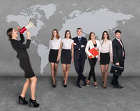 Geschäftsfrauen mit dem Megaphon, das vor Leuten des anderen Sektors steht lizenzfreies stockbild
