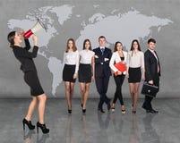 Geschäftsfrauen mit dem Megaphon, das vor Leuten des anderen Sektors steht stockfoto