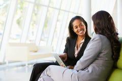 Geschäftsfrauen mit Digital-Tablette, die im modernen Büro sitzt Lizenzfreie Stockfotografie