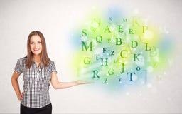 Geschäftsfrauen mit glühendem Buchstabekonzept Stockbilder