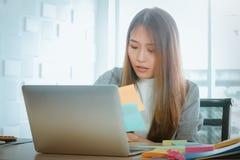 Gesch?ftsfrauen sind bem?ht, zu arbeiten, an dem Schreibtisch, am Computer dort sind klebrige Anmerkungen der Organisation, Sache lizenzfreies stockfoto