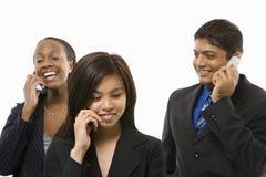 Geschäftsfrauen und Geschäftsmann, die auf Handys sprechen. Lizenzfreie Stockbilder