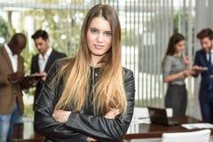 Geschäftsfrauführer, der Kamera im Arbeitsbereich betrachtet lizenzfreie stockfotos
