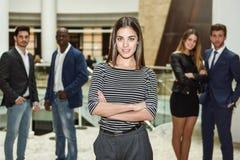 Geschäftsfrauführer, der Kamera im Arbeitsbereich betrachtet stockbild