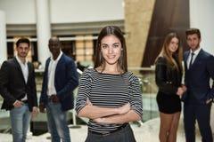 Geschäftsfrauführer, der Kamera im Arbeitsbereich betrachtet stockfotografie
