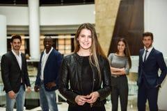 Geschäftsfrauführer, der Kamera im Arbeitsbereich betrachtet stockfotos