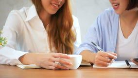 Geschäftsfraugebrauchshandy und -schreiben berichten über Holztisch Asiatin, die Telefon und Tasse Kaffee verwendet