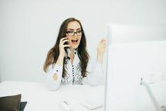 Geschäftsfraugespräch am Telefon und Punkt auf Monitor im Büro Stockbild