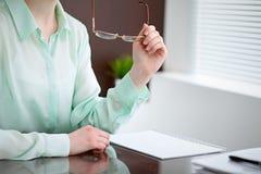 Geschäftsfrauhände in einer grünen Bluse, die am Schreibtisch im Büro sitzt und Gläser, das rechte Fenster hält Sie ist Stockfotos