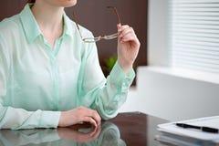 Geschäftsfrauhände in einer grünen Bluse, die am Schreibtisch im Büro sitzt und Gläser, das rechte Fenster hält Sie ist Lizenzfreie Stockbilder