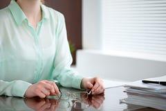Geschäftsfrauhände in einer grünen Bluse, die am Schreibtisch im Büro sitzt und Gläser, das rechte Fenster hält Sie ist Stockfoto