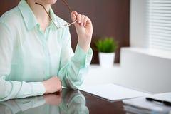 Geschäftsfrauhände in einer grünen Bluse, die am Schreibtisch im Büro sitzt und Gläser, das rechte Fenster hält Sie ist Stockfotografie