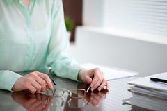 Geschäftsfrauhände in einer grünen Bluse, die am Schreibtisch im Büro sitzt und Gläser, das rechte Fenster hält Sie ist Lizenzfreie Stockfotografie