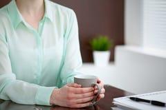 Geschäftsfrauhände in einer grünen Bluse, die am Schreibtisch im Büro sitzt und hält eine graue Schale, rechtes Fenster Stockbilder