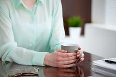 Geschäftsfrauhände in einer grünen Bluse, die am Schreibtisch im Büro sitzt und hält eine graue Schale, rechtes Fenster Stockfotos
