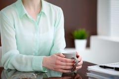 Geschäftsfrauhände in einer grünen Bluse, die am Schreibtisch im Büro sitzt und hält eine graue Schale, rechtes Fenster Lizenzfreie Stockfotografie