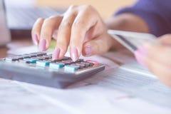 Geschäftsfrauhand, die auf Taschenrechner unter Verwendung ihrer Kreditkarte für online kaufen zählt Lizenzfreie Stockfotos