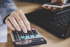 Geschäftsfrauhand, die beim Arbeiten an Computerlaptop anderer Hand hält intelligentes Telefon berechnet Stockfoto