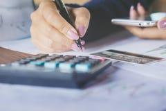 Geschäftsfrauhand, die Monatsausgaben auf Taschenrechner mit Unschärfehintergrund der Kreditkarte und des intelligenten Telefons  Stockfoto
