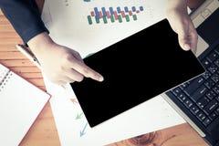 Geschäftsfrauhand, die Tablette hält und Geschäftsbericht analysiert Stockfotografie