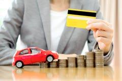 Geschäftsfrauhandgriffkreditkarte, ein Spielzeugauto und ein Stapel Lizenzfreie Stockbilder