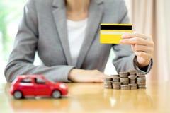 Geschäftsfrauhandgriffkreditkarte, ein Spielzeugauto und ein Stapel Co Lizenzfreie Stockbilder