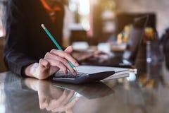 GeschäftsfrauHandpressen auf Taschenrechner für die Rechenkostenschätzung stockfotos