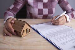Geschäftsfrauhausdokumente zu unterzeichnen lizenzfreie stockfotos