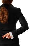 Geschäftsfrauholding kreuzte Finger nach zurück Stockfotografie