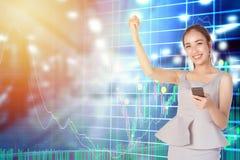 Geschäftsfraukontrolle, die online auf Smartphone mit Grafiken auf Lager auf dem Hintergrund handelt Lizenzfreie Stockbilder
