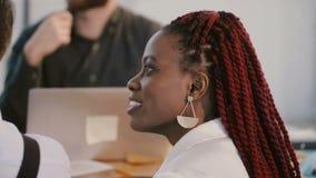 GESCHÄFTSFRAUnicken des jungen positiven Afroamerikaners stimmte das Berufs, hörend Diskussion hinter Tabelle zu stock footage