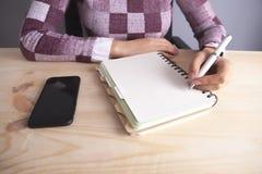 Geschäftsfraunotizbuch-Stift Smartphone auf hölzernem Hintergrund lizenzfreie stockfotografie