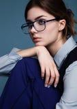 Geschäftsfrauporträt mit Gläsern und blaue Klage mit der Hand unter dem Kinn Stockfotografie