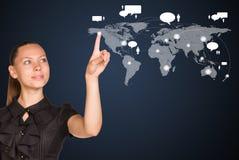 Geschäftsfraupunktfinger an der Weltkarte Stockbilder