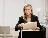 Geschäftsfraurecherchen durch Filedrawer Lizenzfreie Stockfotos