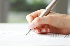 Geschäftsfrauschreiben auf einer Form Stockbilder