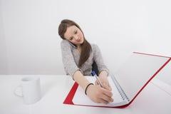 Geschäftsfrauschreibensanmerkungen beim Beantworten des intelligenten Telefons im Büro Stockfotos
