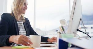 Geschäftsfrautrinkbecher Kaffee beim Arbeiten an Computer stock video