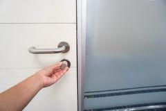 Geschäftsfrauverschluss-Bürotür mit der linken Hand Stockfotografie