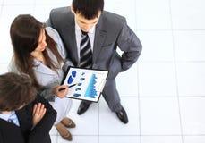 Geschäftsgruppe, die Geschäftsunterlagen bei der Sitzung bespricht Stockfotografie