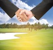 Geschäftshändedruck auf Golfplatz Stockbild