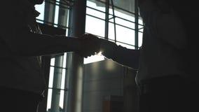 Geschäftshändedruck Innen im Büro mit Sonnenaufflackern am Hintergrund Zwei Geschäftsmänner, die sich grüßen Rütteln des Mannes stock video